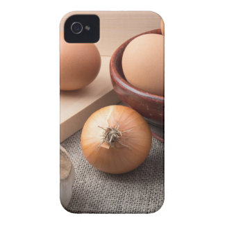 Raw eggs, onions and garlic on a background iPhone 4 case