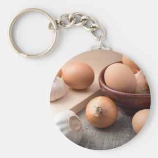 Raw eggs, onions and garlic on a background keychain
