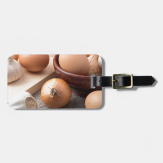 Raw eggs, onions and garlic on a background luggage tag