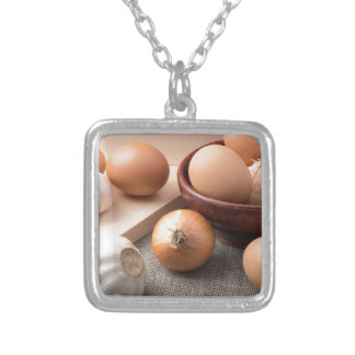 Raw eggs, onions and garlic on a background silver plated necklace