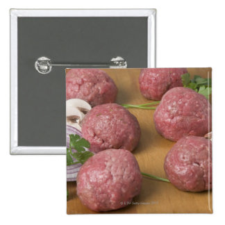 Raw meatballs on a cutting board 2 inch square button