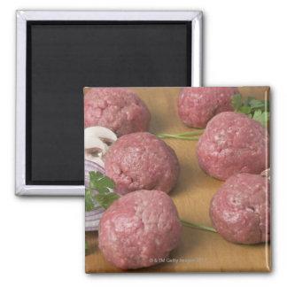 Raw meatballs on a cutting board magnet