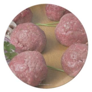 Raw meatballs on a cutting board melamine plate