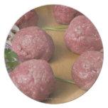 Raw meatballs on a cutting board plates