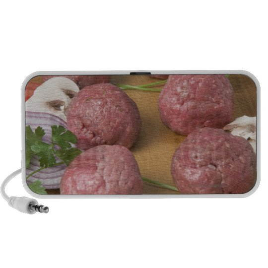 Raw meatballs on a cutting board portable speaker