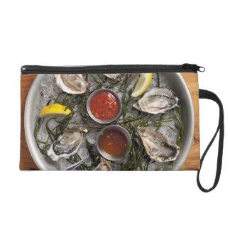 Raw oysters arranged wristlet purse