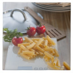Raw pasta on weight scale large square tile