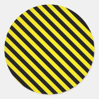 rayas negras amarillas de la precaución bajo pegatina redonda