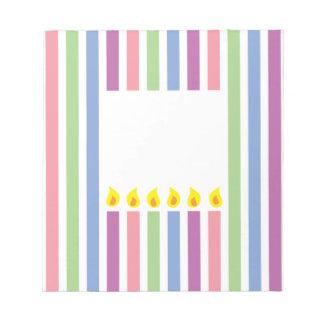 Rayas y velas coloridas en una caja libretas para notas