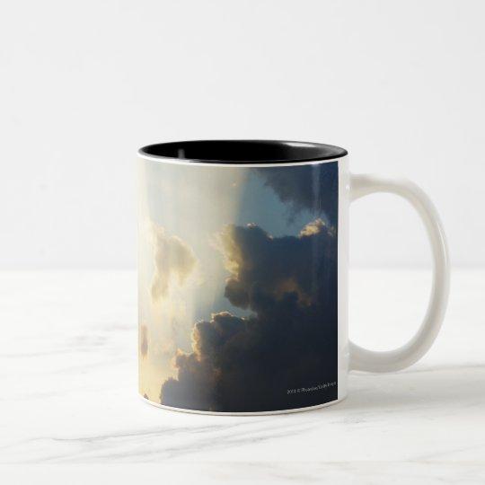 Rayos de la luz que brillan a través de las nubes taza de café de dos colores