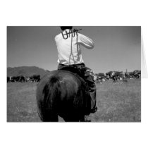 Rear view of a cowboy on a horse with two brands U cards