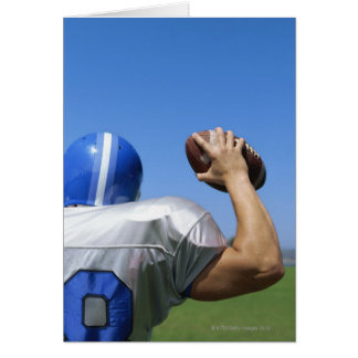 rear view of a football player throwing a card