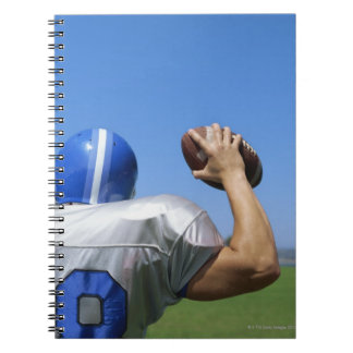 rear view of a football player throwing a spiral notebook