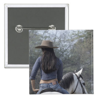 Rear view of a woman riding a horse 2 inch square button