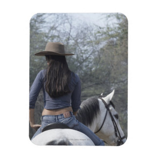 Rear view of a woman riding a horse magnet