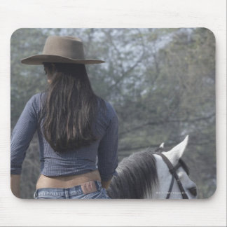 Rear view of a woman riding a horse mouse pad