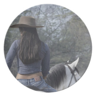 Rear view of a woman riding a horse plates
