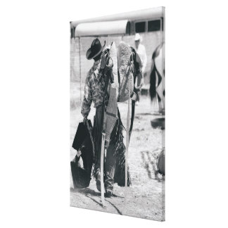 Rear view of cowboy hauling gear canvas print