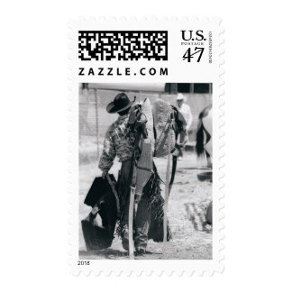 Rear view of cowboy hauling gear postage stamp