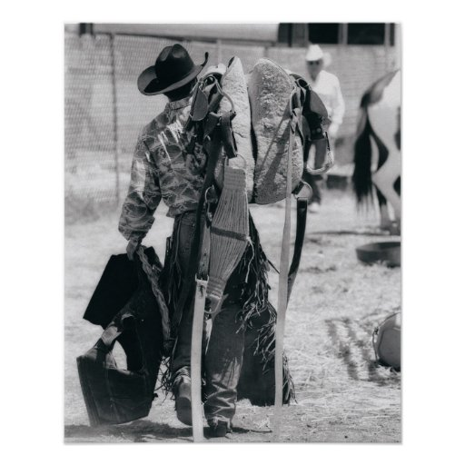 Rear view of cowboy hauling gear posters