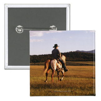 Rear view of cowboy riding horse 2 inch square button