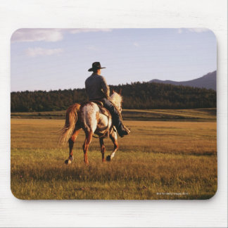 Rear view of cowboy riding horse mouse pad