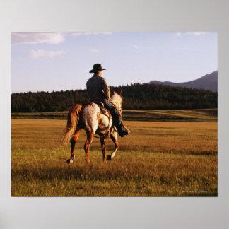 Rear view of cowboy riding horse print