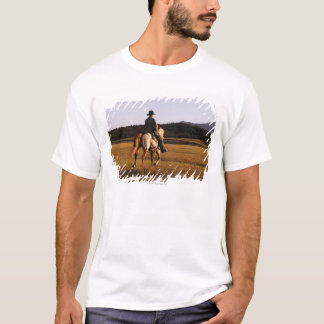 Rear view of cowboy riding horse T-Shirt