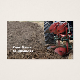Rear view of red plow turning soil business card