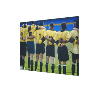 Rear view of rugby team standing with their arms canvas print