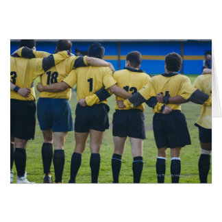 Rear view of rugby team standing with their arms card