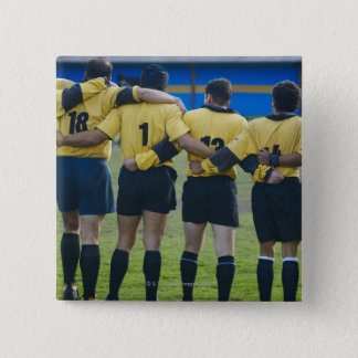 Rear view of rugby team standing with their arms pinback button
