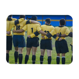 Rear view of rugby team standing with their arms flexible magnets