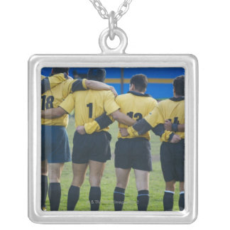 Rear view of rugby team standing with their arms silver plated necklace