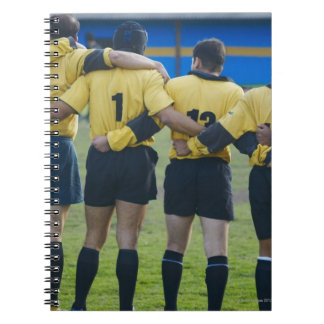 Rear view of rugby team standing with their arms spiral notebook