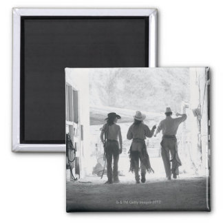 Rear view of three ranch hands leaving stable magnet
