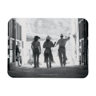 Rear view of three ranch hands leaving stable rectangular photo magnet