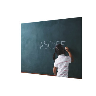 rear view of young girl writing on chalk board canvas print