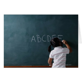 rear view of young girl writing on chalk board card