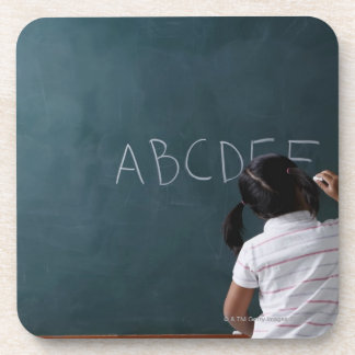 rear view of young girl writing on chalk board coasters