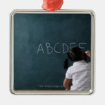 rear view of young girl writing on chalk board ornaments