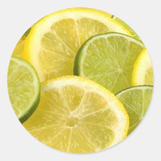 Rebanadas del limón y de la cal pegatina redonda