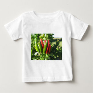 Red and green peppers hanging on the plant baby T-Shirt