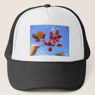 RED AUTUMN LEAVES BRANCH IN HAND TRUCKER HAT