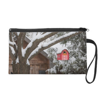 Red barn birdhouse on tree in winter wristlet