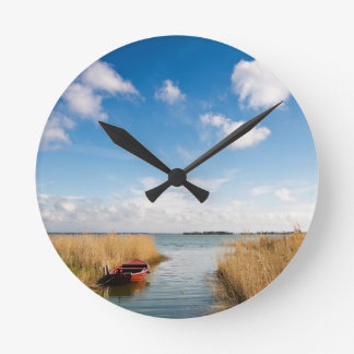 Red boat on a lake with reeds round wall clocks