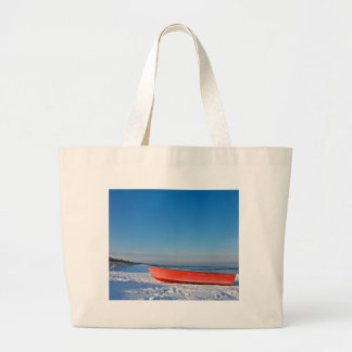 Red boat on shore of the Baltic sea in winter Bags