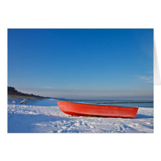 Red boat on shore of the Baltic sea in winter Card