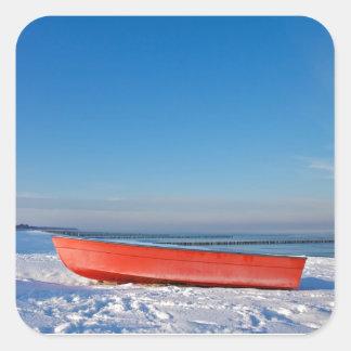 Red boat on shore of the Baltic sea in winter Square Sticker