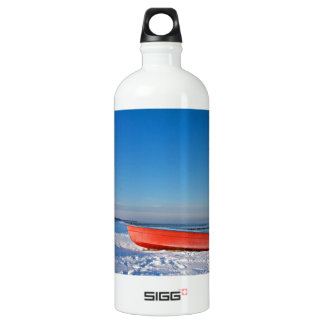 Red boat on shore of the Baltic sea in winter Water Bottle